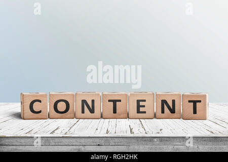 Content sign made of wood on an old table with a blue wall in the background - Stock Image