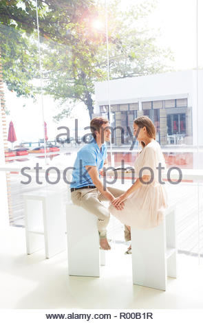 Young couple holding hands while sitting in cafe - Stock Image
