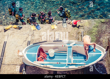 A boat is hauled out of the sea as a group of scuba divers enters the sea - Stock Image