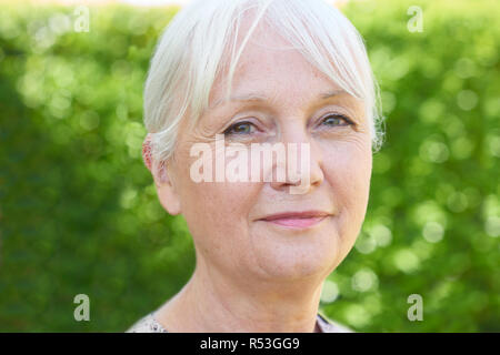 Outdoor Head And Shoulders Portrait Of Serious Senior Woman - Stock Image