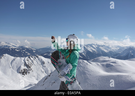 Young female snow boarder photographing mountain view, Mayrhofen, Tyrol, Austria - Stock Image