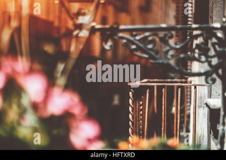 Empty old rusty metal balcony with blurred narrow street behind and lantern with pink flowers in front, historical - Stock Image