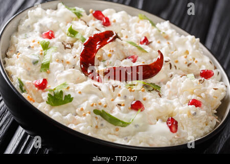 Curd rice or Thayir Sadam is a delicious south Indian recipe where cooked rice is mixed with curd and a tempering is done to it closeup in a plate on - Stock Image