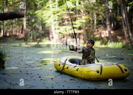 Man holding fish while sitting in inflatable raft on swamp - Stock Image