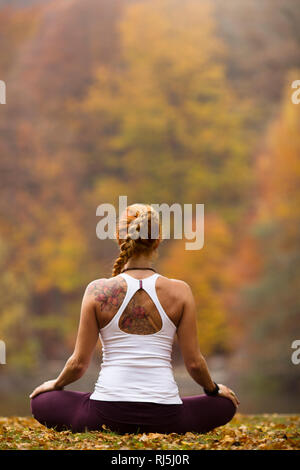 Rear view of woman exercising outdoors - Stock Image