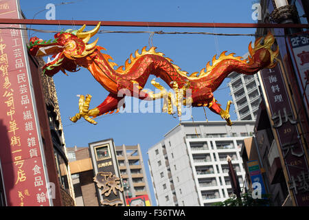 Dragon red and gold kite hung on wire - Stock Image