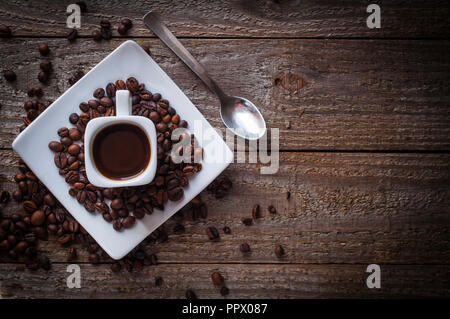 Top view of a square cup of coffee with roasted beans and spoon - Stock Image