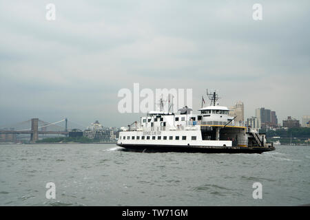 The Governors Island ferry crossing New York harbor on its way from Governors Island to its mooring in the Battery Maritime Building in Manhattan. - Stock Image