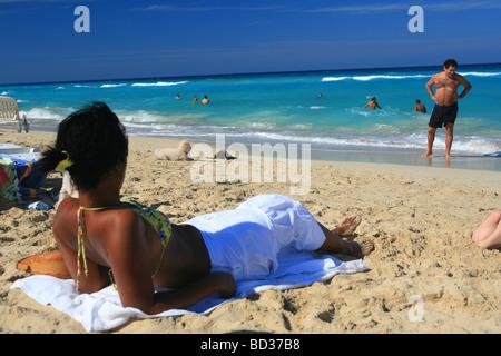 Woman sunbathing near dog  and Caribbean Sea at Playas del Este, near Havana, Cuba. Photo CUBA1043 Copyright Christopher - Stock Image
