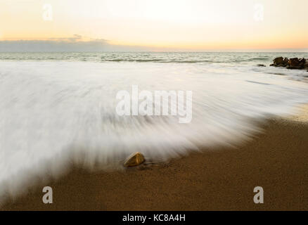 Nature abstract ocean sunset is a beach scene with a captured in time wave rushing to the shore. - Stock Image
