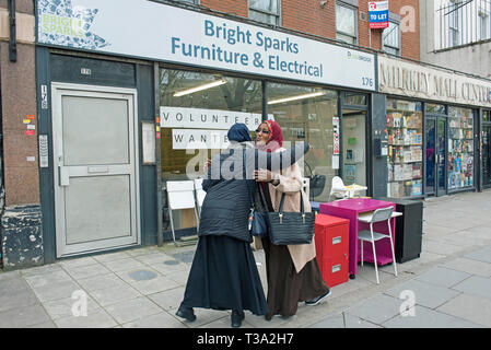 Two ladies greeting each other in the street, Finsbury Park, London Borough of Islington England Britain UK - Stock Image