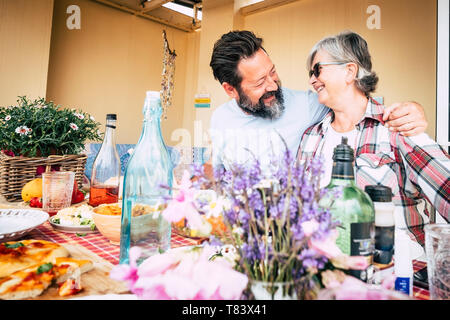 Happy family caucasian people couple mother son senior adult age concept with hug and fun between man and woman smiling - lunch time at home or restau - Stock Image