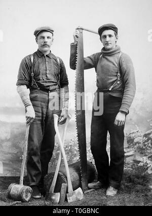 Two lumberjacks pose with the tools of their trade in Wisconsin, ca. 1900. - Stock Image