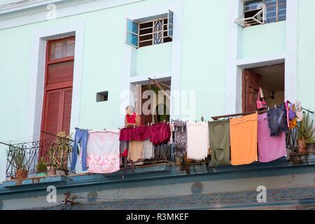 Cuba, Havana. Man and laundry on apartment balcony. Credit as: Wendy Kaveney / Jaynes Gallery / DanitaDelimont.com - Stock Image