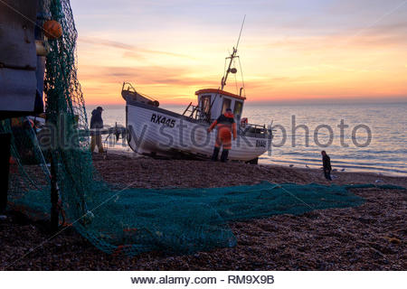Hastings fishing boat being launched at sunrise on a winter day, East Sussex, UK - Stock Image