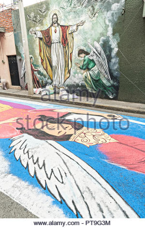A giant floral carpets made from colored sawdust and decorated with flowers decorates the street next to a painted mural of Jesus Christ during the 8th Night Celebration marking the end of the Feast of St Michael in the central Mexican town of Uriangato, Guanajuato. Every year the town decorates 5km of road with religious icons in preparation for the statue of the patron saint to be paraded through the town. Uriangato became an international sensation after wowing Brussels with their floral carpet displayed at the Brussels Grand-Place during the Belgium Floral Carpet festival. - Stock Image
