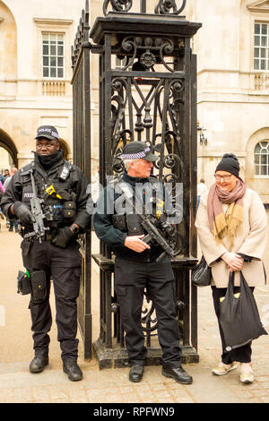 Armed police guard talk to Elderly lady while patrolling the entrance to Horse guards parade in Whitehall London England - Stock Image