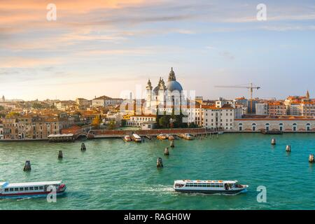 Vaporetto and boats cross the grand canal with the dome of Santa Maria Della Salute Cathedral in the distance as the sun goes down in Venice, Italy - Stock Image