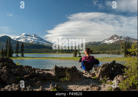 Model Released.  A young woman and her dog enjoy the view of the South Sister at the Ray Atkeson memorial viewpoint on Oregon's Sparks Lake - Stock Image