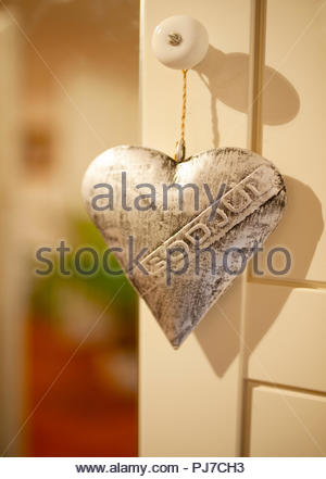 A silver heart  ornament saying 'God Jul', which is Swedish for Merrry Christmas. Ornament hanging on open door, red and green colours through there. - Stock Image
