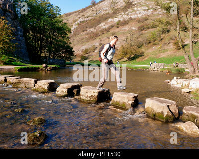 Peak District National Park, Derbyshire, UK. 10th October, 2018. UK Weather Woman crossing the stepping stones on an unusually hot sunny October day in the tourist hotspot of Dovedale in the Peak District National Park, Derbyshire Credit: Doug Blane/Alamy Live News - Stock Image
