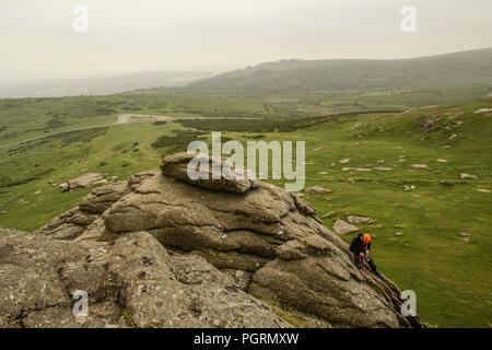 A man abseils down the face of Haytor Rocks in Dartmoor National Park - Stock Image