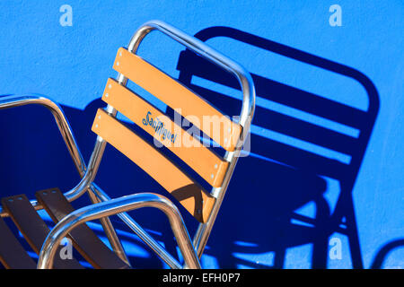 Strong graphic image of San Miguel branded frame chair and sunlight casting shadow on blue wall - Stock Image