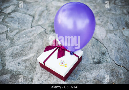 Gift box with a purple bow and balloon - Stock Image
