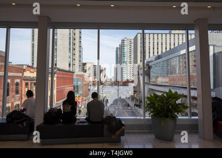 OTTAWA, CANADA - NOVEMBER 11, 2018: Group of Canadians observing Rideau street from the windows of a building with typical residential towers and hist - Stock Image