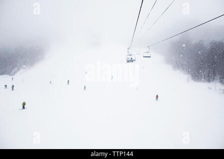 Low angle view of ski lift over snow covered field - Stock Image