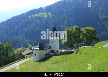 Church and trees in Mutten, Switzerland. - Stock Image
