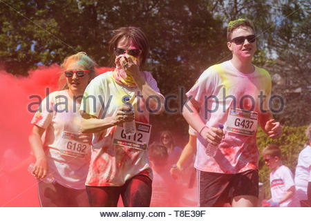 Garstang, UK, 12 May 2019. Participants get covered in paint at the Garstang Colour Dash, a 5km fun run filled with colour on a glorious sunny day. The popular event raised money for St Johns Hospice, a local independent charity providing care and support for patients and families living with life shortening conditions in North Lancashire and South Lakes.   Credit Keith Douglas News/Alamy Live News - Stock Image
