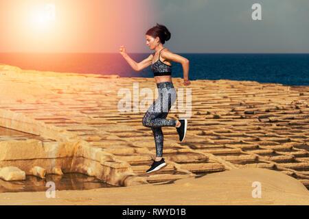 woman runner, running across limestone salt pans in Malta. - Stock Image