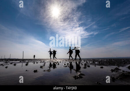 Pilgrims carrying crosses to the Holy Island of Lindisfarne in Northumberland during the annual Christian Easter pilgrimage on Good Friday. - Stock Image
