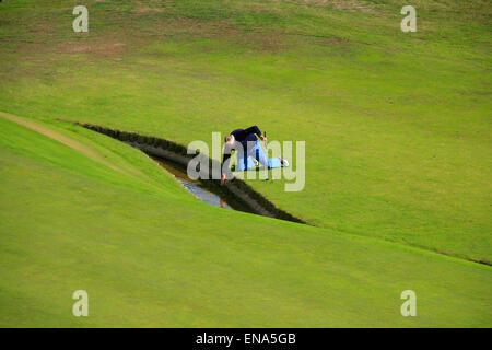 Golfer retrieving ball from stream. - Stock Image