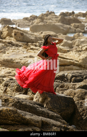 African Woman with Dreadlocks, Wearing a Red Dress, Standing on Rocks by the Sea. - Stock Image