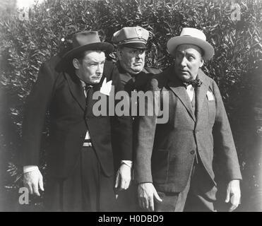 Policeman arresting two men - Stock Image