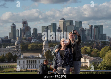 London Panorama from Greenwich Park, England UK. 22 September 2018 Taking selfie photographs with Canary Wharf as a backdrop. 20th and 21st cntury Can - Stock Image