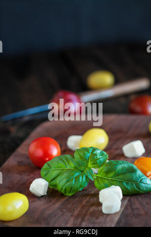 Fresh from the garden basil and heirloom tomatoes with mozzarella cheese for caprese salad, Italian food and healthy vegetarian diet concept, over a r - Stock Image