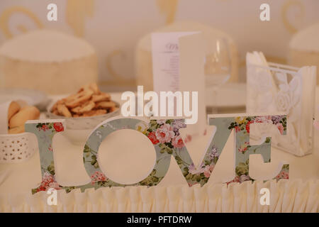 Stand alone letters plaque with vintage floral embellishment, that reads Love, positioned on bride and groom's table, at a wedding or engagement party - Stock Image