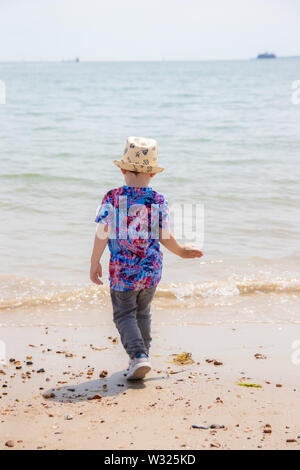 A small boy in summer clothing playing at the seaside in summer wearing a summer hat - Stock Image