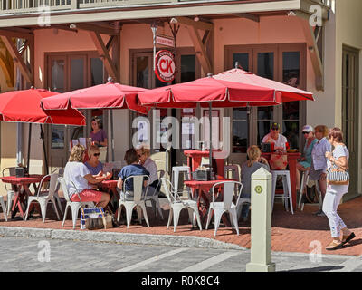 Sidewalk cafe or restaurant with senior adult mature women eating lunch under umbrellas at The Cowgirl Kitchen in Rosemary Beach Florida, USA. - Stock Image