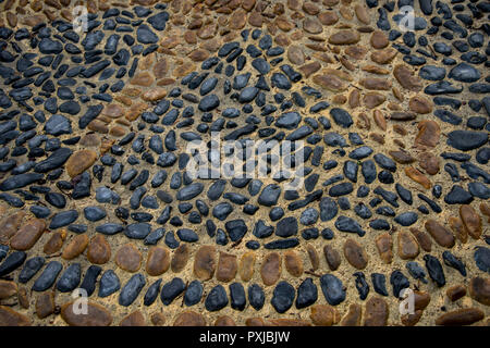stones of different colors set in a pattern on a pavement in Monforte d'Alba in Italy - Stock Image