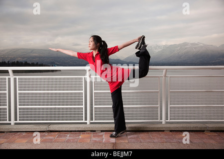 A young Asian woman does the Natarajasana Lord of the Dance yoga pose at Canada Place, Vancouver, British Columbia, - Stock Image