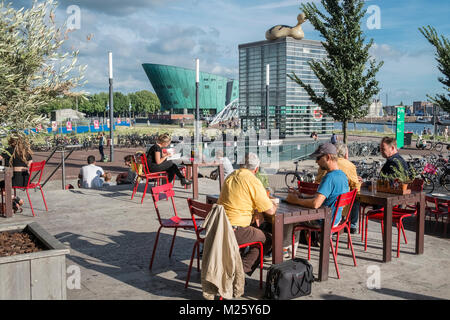 People sitting in sunshine outside the Public Library of Amsterdam, with NEMO Science Museum in the background, - Stock Image
