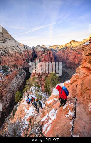 Young woman hikes on the via ferrata descending from Angels Landing, Angels Landing Trail, in winter, Zion Canyon - Stock Image