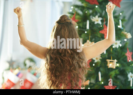 Seen from behind young woman in red dress near Christmas tree rejoicing - Stock Image