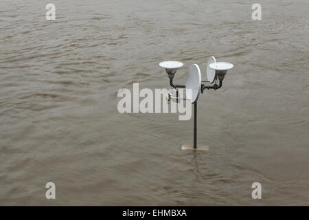 Street lamppost with a satellite dish partially flooded by the swollen Vltava River in Prague, Czech Republic. - Stock Image