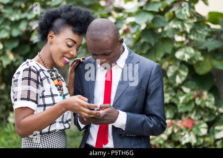 Young people happy to consult together a mobile phone to the outdoors. - Stock Image