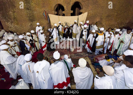 Priests chanting prayers in the courtyard of Bet Medhane Alem church, during the prayers on Ethiopian Easter Saturday, Lalibela, Ethiopia - Stock Image